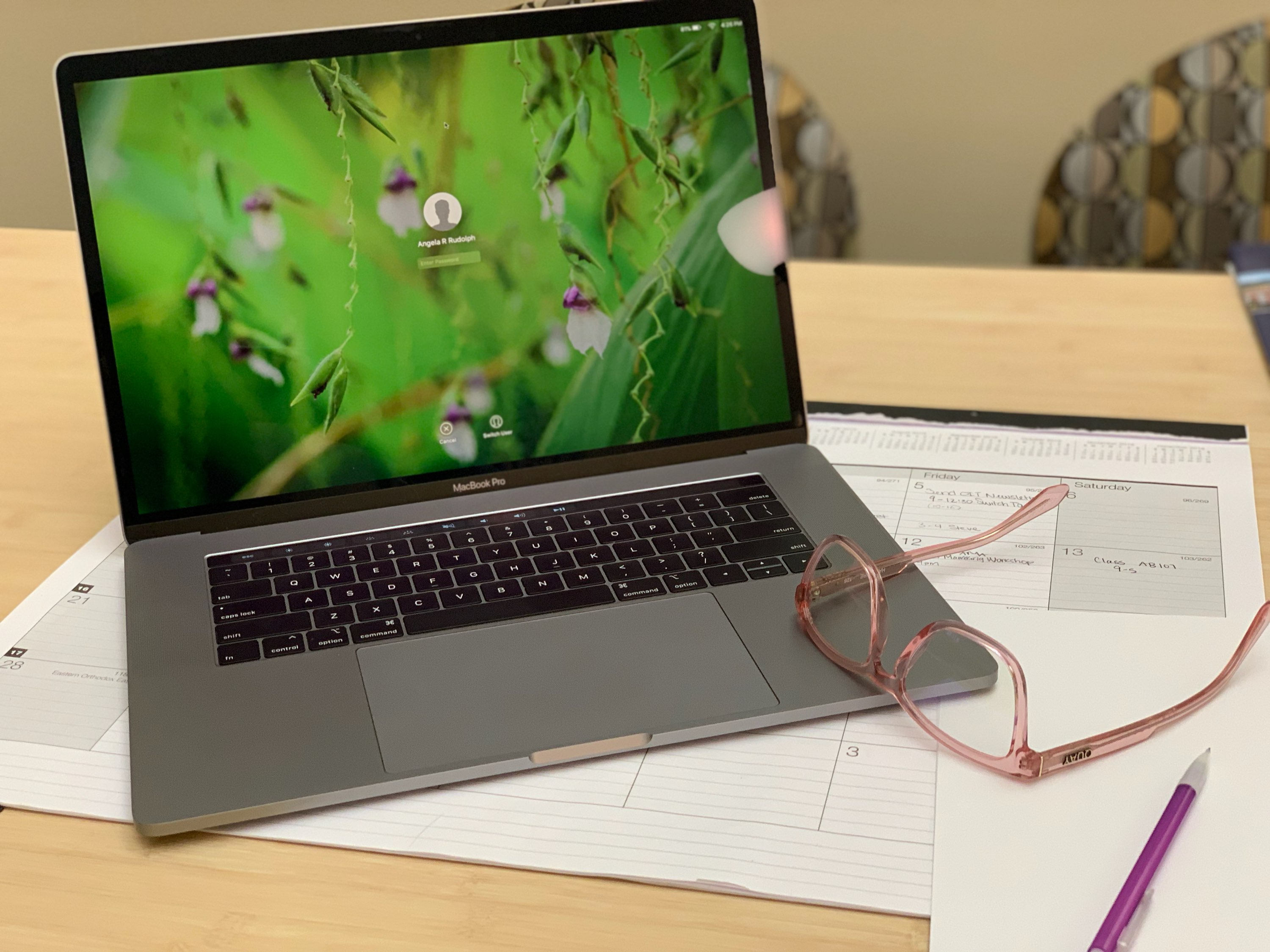 Computer on desk with glasses and paper nearby
