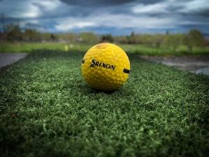 Golf ball on a driving range mat