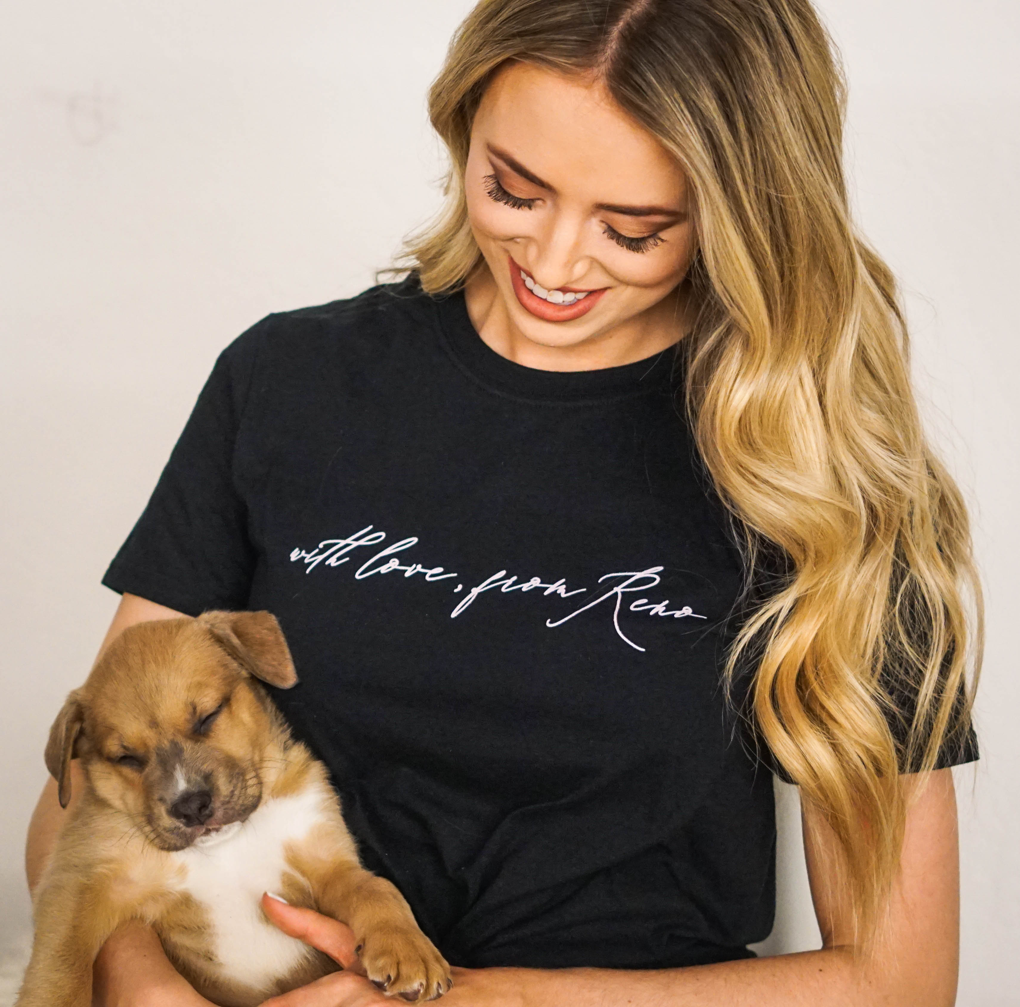 Woman in a t-shirt from a local clothing store holding a sleeping puppy from the SPCA.