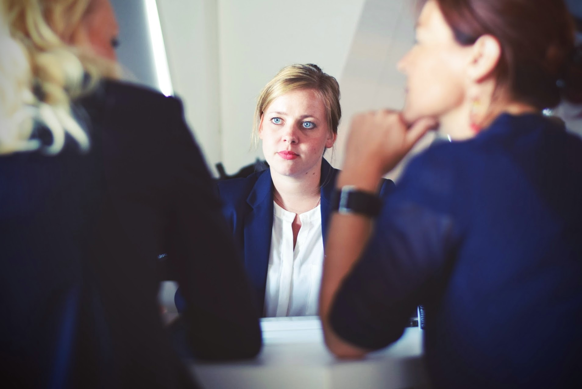 Woman looking at two business people talking