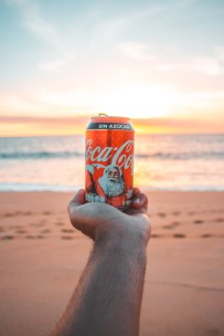 A Christmas Coke can someone is holding on the beach.