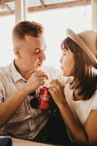 Man and woman staring at one another lovingly while sipping from the same coke can.
