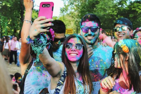 Group covered in paint smiling and taking a picture on a cell phone.