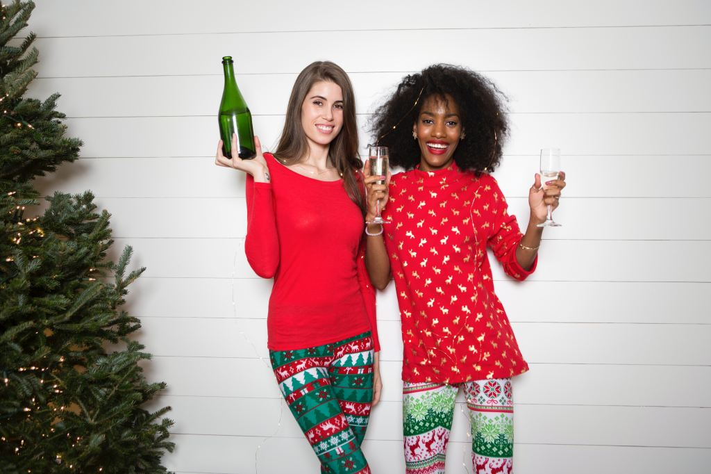 Two ladies dressed in Christmas outfits near a tree with champagne.