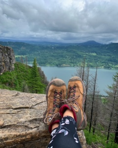 Landscape shot of the columbia river gorge with trees and the river and a pair of legs with hiking boots lounging on top of a rock.